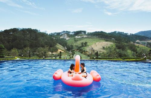 """Vì sao nó xứng đáng để xuất hiện đầu danh sách những thứ nên trải nghiệm khi đến khu nghỉ dưỡng này? Check-in khu nghỉ dưỡng có hồ bơi ngắm đồi núi sống ảo """"hot"""" nhất Đà Lạt - Ảnh 7. Hồ có kích thước cực rộng, lại đặt ở một vị trí không thể đẹp hơn. Một bên view hồ hướng thẳng ra đồi thông xanh ngắt, không gian xung quanh thoáng đãng. Từ hồ bơi bạn có thể hướng mắt ra xa nhất để ngắm múi non trùng điệp, ngước mặt lên trên là bầu trời thăm thẳm, hướng phía dưới là sân golf trải dài như tấm thảm mượt mà, còn sau lưng bạn là một dãy những căn phòng xinh xắn của resort. Vừa nhìn thấy là cả bọn đã muốn lao xuống cái hồ bơi tuyệt đẹp ấy ngay tức thì. Cảm giác đầu tiên khi bạn bước một chân xuống nước sẽ hơi lạnh một chút, nhưng chỉ cần bước thêm chân thứ hai và dần dần để cả người ngập trong nước thì mọi thứ không thể ổn hơn. Vài giây sau khi đầm mình trong hồ, tôi đã quên rằng mình đang ở nơi mà nền nhiệt chỉ 17 đến 25 độ C và xung quanh toàn là núi non. Mặt trời buổi sáng đã sưởi ấm nước hồ một cách tự nhiên. Diện bikini được dặn mang theo từ đầu chuyến đi, mấy đứa con gái chúng tôi cùng thả người khoan khoái trên chiếc phao lớn hình con hồng hạc thả trôi tự do trong hồ, tận tưởng làn gió cao nguyên dịu nhẹ sượt qua trên da, chân phe phẩy nghịch nước… và ngắm nhìn khung cảnh vừa thơ mộng vừa hùng vĩ xung quanh. Nước trong hồ bơi ở Swiss-Belresort Tuyền Lâm, Đà Lạt mát nhưng không hề lạnh như mọi người thường nghĩ về xứ cao nguyên. Buổi trưa khi những vạt nắng chiếu xuyên đồi thông, bạn còn cảm thấy không khí xung quanh và cả mặt nước hơi âm ấm nữa cơ."""